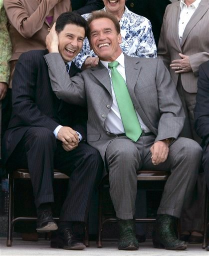 In this June 13, 2007, file photo, former Gov. Arnold Schwarzenegger, right, and former Assembly Speaker Fabian Nunez, D-Los Angeles, joke around before a legislative group photo is taken at the Capitol in Sacramento, Calif.