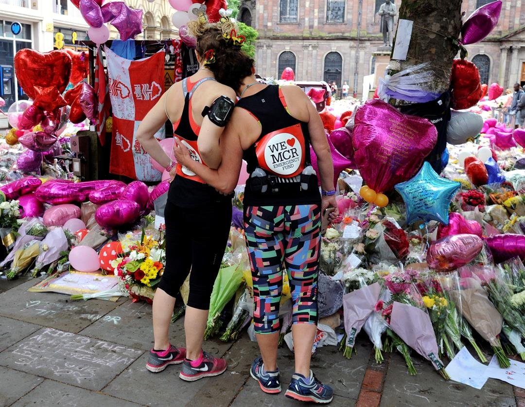 Marathon runners pay respect at flower tributes in St Ann's square, before the Great Manchester Run in Manchester, England Sunday, May 28, 2017. (AP Photo/Rui Vieira)