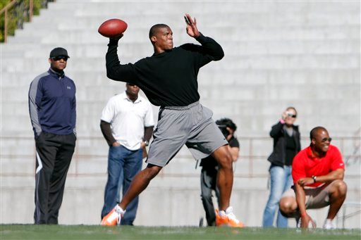 NFL draft prospect Cam Newton throws a pass while trainers and members of the media look on during a football workout Thursday, Feb. 10, 2011, in San Diego. (AP Photo/Chris Park)