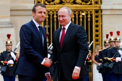 Russian President Vladimir Putin, right, is welcomed by French President Emmanuel Macron at the Palace of Versailles, near Paris, France, Monday, May 29, 2017. (AP Photo/Alexander Zemlianichenko, pool)