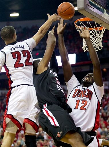 San Diego State's Billy White, center, shoots against UNLV's Chace Stanback. left, and Brice Massamba in the first half during an NCAA college basketball game, Saturday, Feb. 12, 2011, in Las Vegas. (AP Photo/Julie Jacobson)