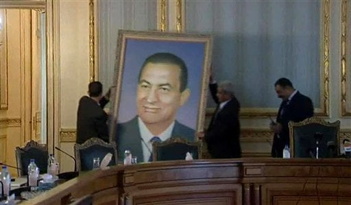 In this frame from video , officials remove a portrait of ousted Egyptian President Hosni Mubarak at the main Cabinet building in Cairo, on Sunday, Feb. 13 2011. (AP Photo / APTN)
