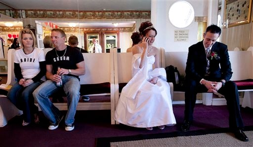 Becky Kulak, second from right, of Richfield, Minn., talks on the phone with her new father-in-law after marrying Jeff Kulak, right, as Becky, far left, and Jason Kucera, of Enid, Okla., wait their turn to be married at the Little White Wedding Chapel.