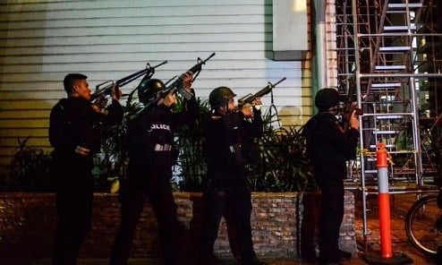 Filipino elite Police Special Weapons and Tactical (SWAT) personnel take their position outside the Resort World Manila hotel.