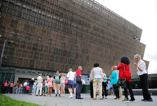 FILE- In this May 1, 2017, file photo, people wait in line to enter the Smithsonian National Museum of African American History and Cultural on the National Mall in Washington. (AP Photo/Pablo Martinez Monsivais, File)