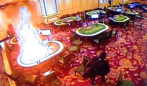 A gunman walks away after setting fire to a gambling table in the Resorts World Manila entertainment and gambling complex.