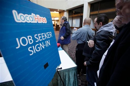 In this Jan. 26, 2011 photo, job seekers line up for a job fair at a hotel in Dallas. (AP Photo/LM Otero)