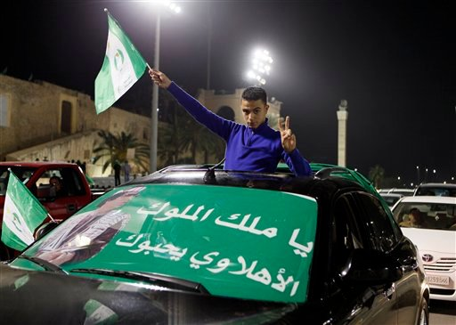 A supporter of Libyan President Moammar Gadhafi posses for the camera while holding a flag during a pro-government demonstration in Tripoli early Feb. 17, 2011. (AP Photo/Abdel Meguid al-Fergany)