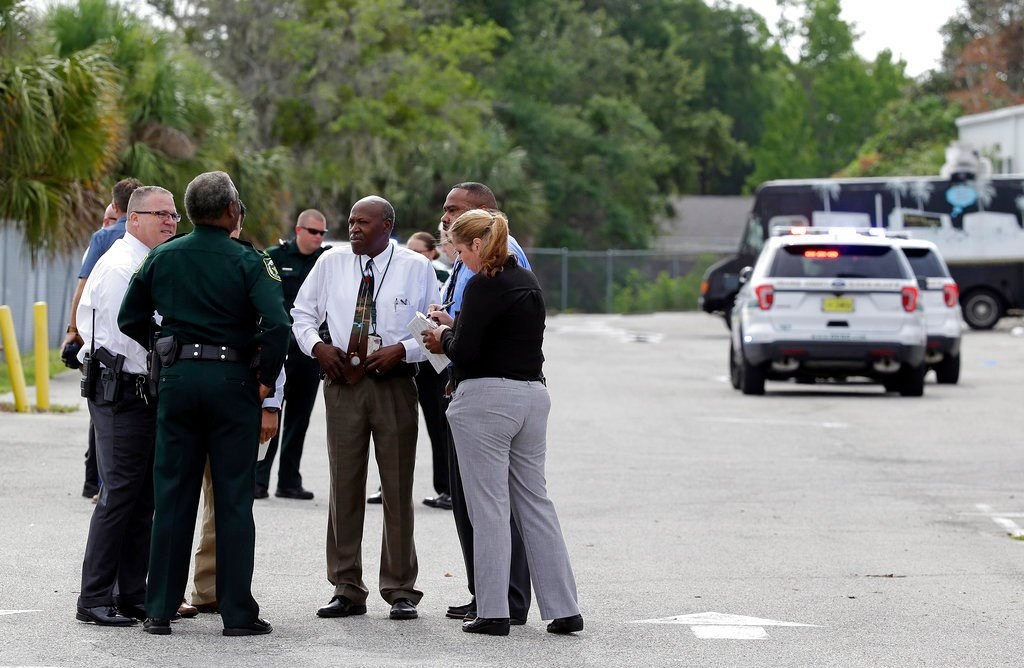Authorities confer near the scene of a shooting where they said there were multiple fatalities in an industrial area near Orlando, Fla., Monday, June 5, 2017. (AP Photo/John Raoux)