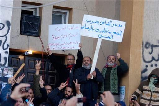 This photograph, obtained by The Associated Press outside Libya and taken by an individual not employed by AP, shows people shouting and holding signs during recent days' unrest in Benghazi, Libya.
