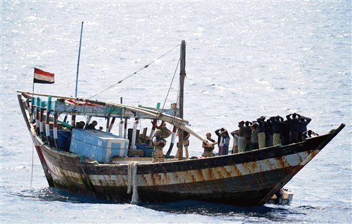 In this image made available by the Ministry of Defence in London, Thursday Feb. 16, 2011, a naval boarding party from HMS Cornwall guard Somali pirates after their dhow was boarded in the Indian Ocean on Thursday Feb. 10, 2011. (AP)