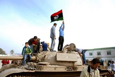 Residents stand on a tank holding a pre-Gadhafi era national flag inside a security forces compound in Benghazi, Libya on Monday, Feb. 21, 2011.