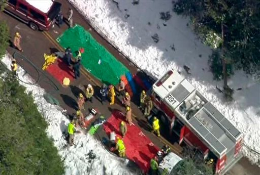 This video image provided by CBS2/KCAL9 News shows rescue efforts after a school bus carrying up to 25 children aboard slid over the side of a highway in a Southern California ski area near Twin Peaks, Calif., after colliding with a county fire vehicle.