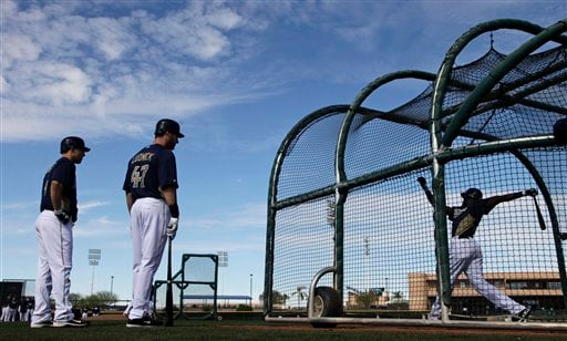 San Diego Padres' Ryan Ludwick, center, and Nick Hundley, left, wait their turn while Cameron Maybin hits during batting practice at baseball spring training Monday, Feb. 21, 2011, in Peoria, Ariz.