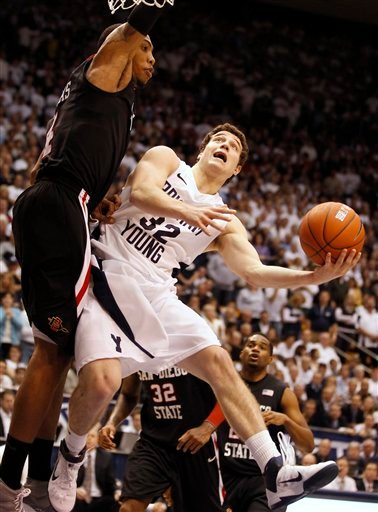 BYU's Jimmer Fredette, right, scoops a shot over San Diego State's Malcolm Thomas during the second half of an NCAA college basketball game in Provo, Utah, Wednesday, Jan. 26, 2011.