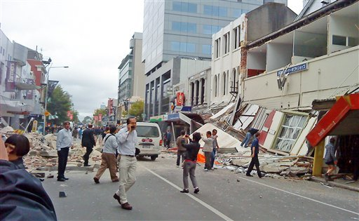 In this photo released by China's Xinhua News Agency, people walk through a street partly covered with rubble after an earthquake hit Christchurch, New Zealand, Tuesday, Feb. 22, 2011.
