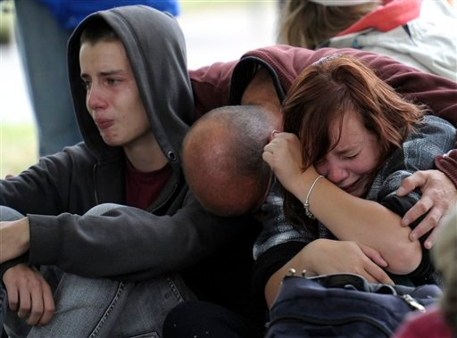 Fifteen-year-old Kent Manning, left, and his sister Lizzy, 18, react with their father, who asked not to identified, after they were told by police that there was no hope of finding Kent and Lizzy's mother alive in a collapsed building.