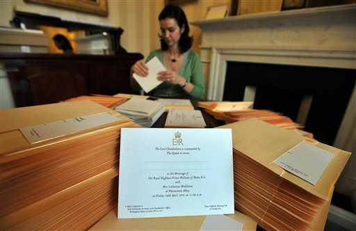 In this photo taken Wednesday Feb. 16, 2011 at Buckingham Palace in London, a member of the Lord Chamberlain's Office, no name given, places invitations into envelopes, to the wedding of Prince William and Kate Middleton.