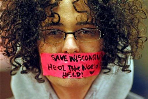 Kathryn Schulze wears a message written on tape over her mouth inside the state Capitol Monday, Feb. 21, 2011, in Madison, Wis.