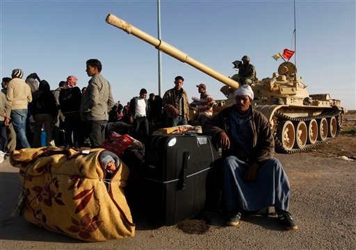 Egyptians who fled from Libya through the Salloum land port gate wait with their belongings next to an Egyptian armored vehicle at the Egyptian-Libyan border, in Salloum, Egypt, Tuesday, Feb. 22, 2011.