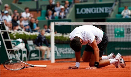 Serbia's Novak Djokovic falls as he plays Austria's Dominic Thiem during their quarterfinal match the French Open.