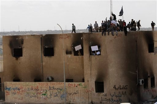 Libyan protesters stand on the rooftop of a burned police station, during a demonstration against their Libyan Leader Muammar Qaddafi, in Tobruk, Libya, Wednesday Feb. 23, 2011. (AP Photo/Hussein Malla)