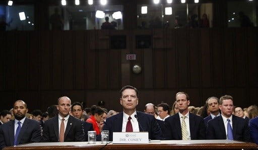 Former FBI director James Comey listens to the committee chairman at the beginning of the Senate Intelligence Committee hearing on Capitol Hill.