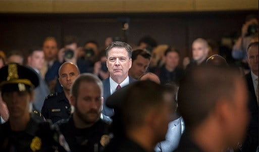 Former FBI director James Comey walks through a corridor on the way to a secure room to continue his testimony.