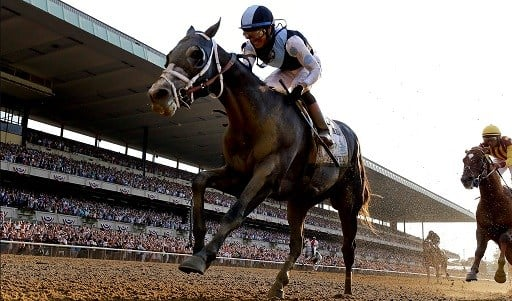 Tapwrit, ridden by Jose Ortiz crosses the finish line to win the 149th running of the Belmont Stakes horse race.