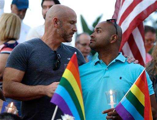 Supporters of the victims of the recent mass shooting at the Pulse nightclub hold flags and candles at a vigil at Lake Eola Park, Sunday, June 19, 2016, Orlando, Fla. Tens of thousands of people attended the vigil. (AP Photo/John Raoux)