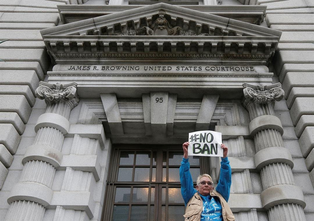 In this Feb. 7, 2017, file photo, Karen Shore holds up a sign outside of the 9th U.S. Circuit Court of Appeals in San Francisco, Calif. (AP Photo/Jeff Chiu, file)