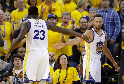 Golden State Warriors forward Draymond Green (23) and guard Stephen Curry (30) celebrate during the second half of Game 5 of basketball's NBA Finals against the Cleveland Cavaliers in Oakland, Calif., Monday, June 12, 2017. (AP Photo/Marcio Jose Sanchez)