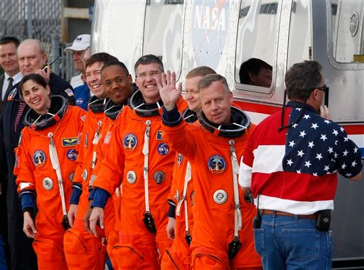 Commander Steve Lindsey, right, waves as he and the crew of space shuttle Discovery, leave the Operations and Checkout Building to board the shuttle at pad 39A, Thursday, Feb. 24, 2011.