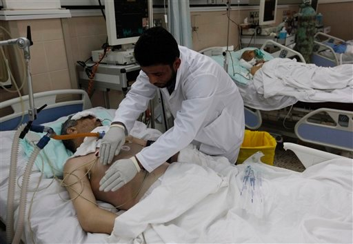 A Libyan doctor treats a wonded man who was injured last week during the demostration against Libyan leader Moammar Gadhafi, in Benghazi, Libya, on Thursday Feb. 24, 20011. (AP Photo/Hussein Malla)