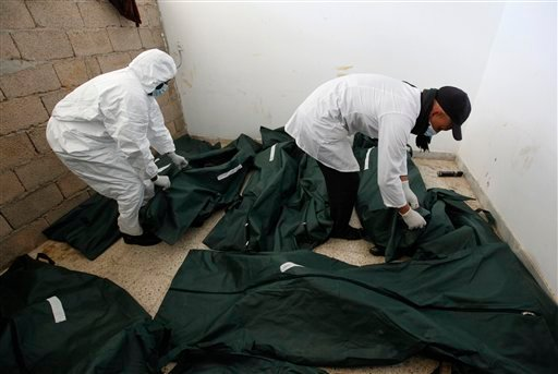 Libyan mortuary assisstants look to unidentified dead burned bodies who were killed last week during the demonstration against Libyan leader Moammar Gadhafi at a morgue hospital, in Benghazi, Libya, on Thursday Feb. 24, 2011. (AP Photo/Hussein Malla)