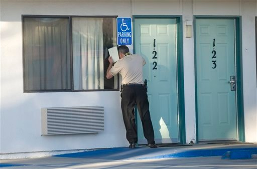 A police investigator knocks on doors at the Motel 6 in Stanton, Calif. on Friday, Jan. 28, 2011. Deputies responding to reports of suspicious activity found a man's and a woman's body in and near the motel.