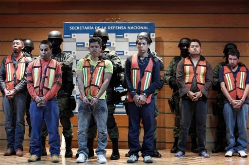 "Soldiers escort Julian Zapata Espinosa, aka ""El Piolin"", third left, alleged member of the Los Zetas drug cartel and main suspect in the killing of U.S. Immigration and Customs, ICE, agent Jaime Zapata, during a presentation for the media in Mexico City."