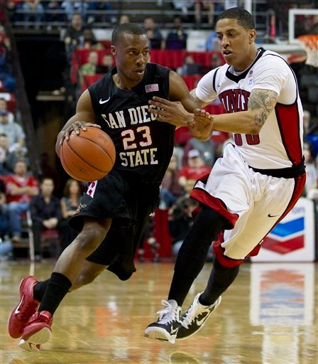 San Diego State's D.J. Gay, left, drives to the basket against UNLV's Tre'Von Willis in the first half during an NCAA college basketball game, Saturday, Feb. 12, 2011, in Las Vegas.