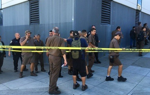 UPS workers gather outside after a reported shooting at a UPS warehouse and customer service center in San Francisco.