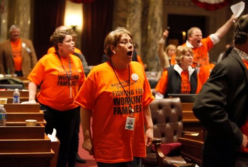 State Rep. Christine Sinicki, D-Milwaukee, and other Assembly Democrats approach the front of the chamber in outrage as their Republican counterparts cut off debate and voted on the budget repair bill in session at the state Capitol in Madison, Wis. (AP)