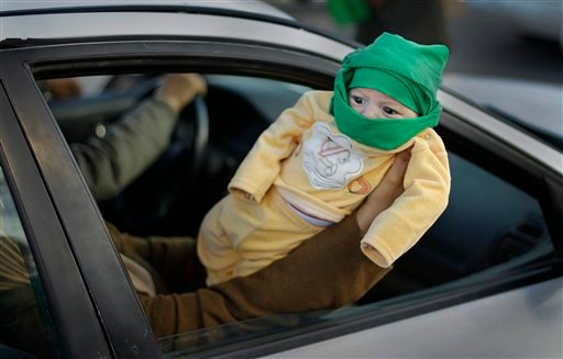 """A pro-Gadhafi supporter holds her baby wearing a green mask, the color of the national flag and the Libyan Leader's """"Green Book"""", out of a car window for others to see as they pass a pro-regime rally of around 100 supporters. (AP)"""