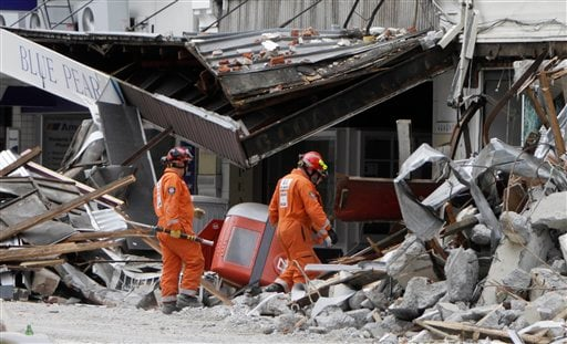 Representatives from the United Kingdom Fire and Rescue Service inspect the earthquake-damaged buildings in Colombo Street, Christchurch, New Zealand, Saturday, Feb. 26, 2011. (AP Photo/Mark Baker)