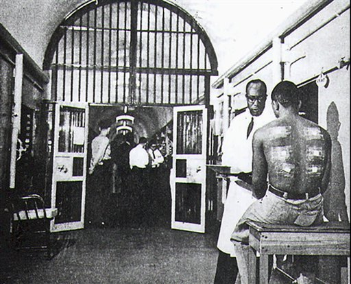 In this Feb, 1966 picture, Solomon McBride, second right, a medical administrator of Holmesburg Prison's human research, questions a test subject at the facility in Philadelphia.