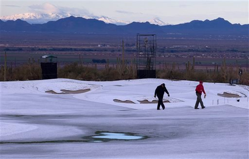 Superintendents at the Ritz Carlton Golf Club check the playing surface on the second fairway for saturation levels after snow fell early in the morning. (AP Photo/Julie Jacobson)