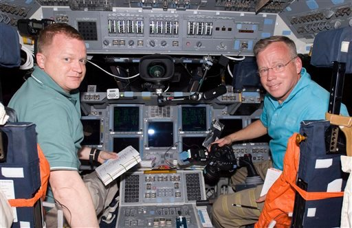 In this Friday, Feb. 25, 2011 photo provided by NASA, on space shuttle Discovery's forward flight deck, astronauts Steve Lindsey, right, STS-133 commander, and Eric Boe, pilot, switch seats for a brief procedure. (AP Photo/NASA)