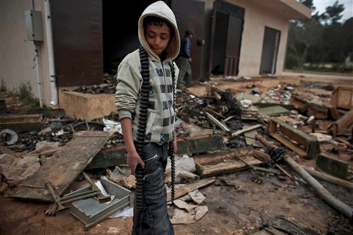 A Libyan boy with an empty ammunition belt surveys destroyed weapons boxes at a burned out army base in the eastern town of Shahat, Libya Feb. 28, 2011. (AP Photo/Tara Todras-Whitehill)