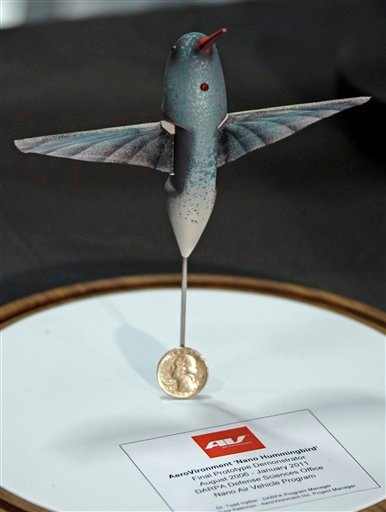 """A tiny, drone aircraft designed to mimic a hummingbird, known as the """"nano-hummingbird,"""" is seen with a quarter for scale, during a briefing at the AeroVironment facility in Simi Valley, Calif., Friday, Feb. 25, 2011."""