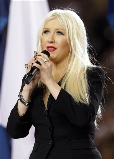 FILE - In this Feb. 6, 2011 file photo, Christina Aguilera sings the national anthem before the NFL football Super Bowl XLV game between the Green Bay Packers and the Pittsburgh Steelers in Arlington, Texas.