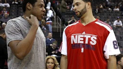 New Jersey Nets point guard Deron Williams, right, talks with rapper Jay-Z as singer Beyoncé Knowles, center, is seen court side. (AP Photo/Julio Cortez)