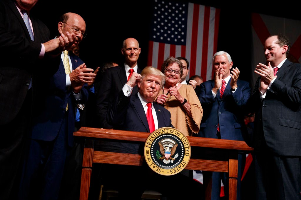 President Donald Trump pumps his fist after signing an executive order on Cuba policy, Friday, June 16, 2017, in Miami. From left are, Commerce Secretary Wilbur Ross, Florida Gov. Rick Scott, Cary Roque, Vice President Mike Pence and Labor Secretary Alex